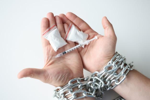Man gebonden handen in ketting houdt een pakket drugs vast en motiveert drugsverslaafden om te stoppen met het gebruik van drugs