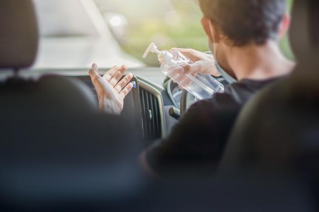 Man gebruikt alcoholgel 70% om hand in auto te reinigen om corona-virus 2019 of covid 19 te beschermen