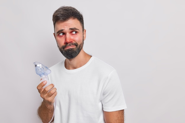 Man gebruikt medische apparatuur voor inademing heeft astma-aanval allergische reactie rode gezwollen ogen kijkt verdrietig weg staat op wit