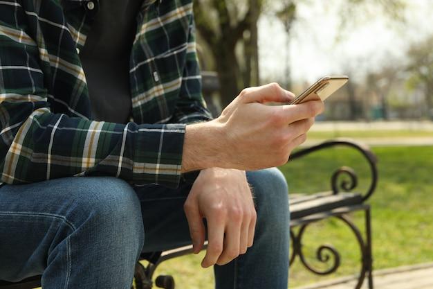 Man gebruikt smartphone zittend op een bankje in het park