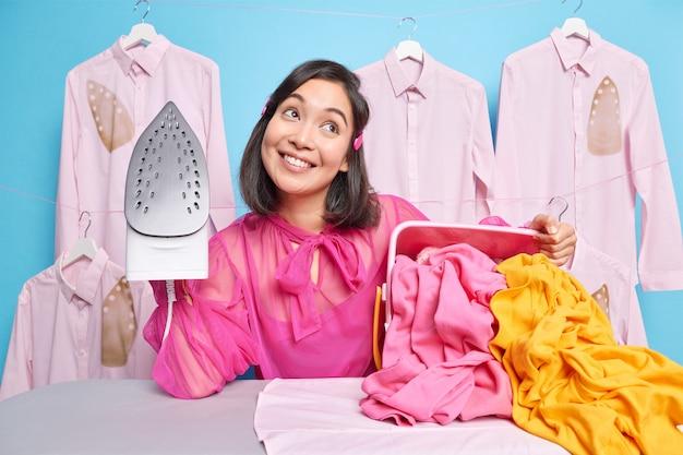 Man geconcentreerd boven gaat strijken thuis houdt stoomstrijkijzer denkt na over plannen na het afronden van huishoudelijk werk