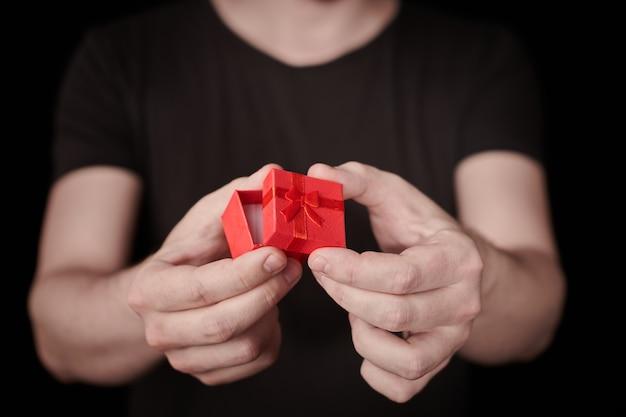 Man geeft een geschenk in rode geschenkdoos. valentijnscadeau openen. kleine jubileumgeschenkdoos van de mens. klein verrassingsconcept. zwarte achtergrond.