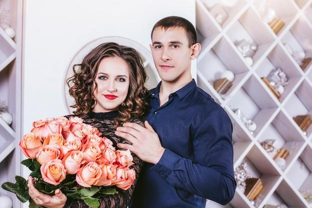 Man geeft een vrouw een boeket bloemen in het interieur van het huis