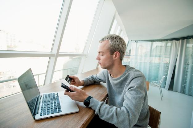 Man geeft nummer van zijn creditcard aan de klant om betaling voor het werk te ontvangen. witte kamer met panoramische ramen op de achtergrond. salaris tijd concept. freelance baanconcept.