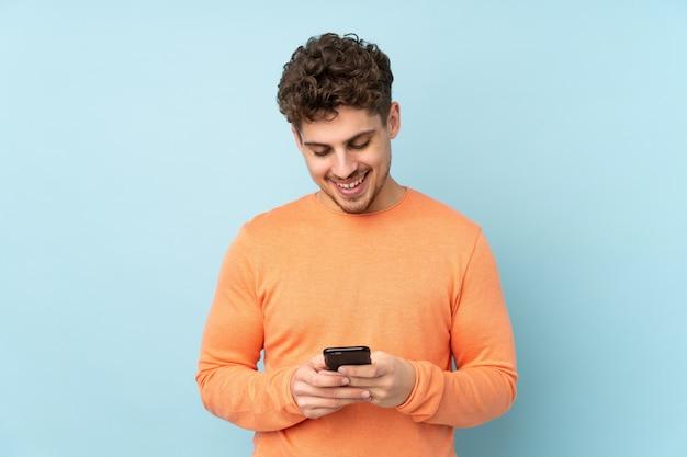 Man geïsoleerd op blauwe muur verzenden van een bericht met de mobiel