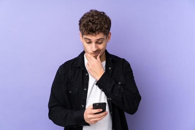 Man geïsoleerd op paarse muur denken en het verzenden van een bericht