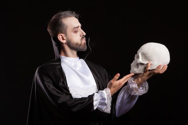 Man gekleed in dracula kostuum voor halloween kijken naar een menselijke schedel. man met vampiertanden. spooky man met halloween kostuum.