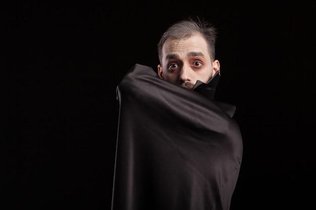 Man gekleed in dracula kostuum voor halloween verstopt achter zijn cape. boze man in dracula-kostuum. griezelige vampier.