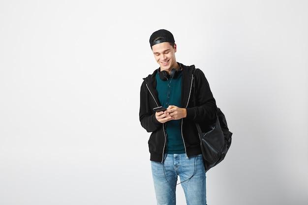 Man gekleed in een donkere t-shirtjeans-sweatshirt en een pet gebruikt mobiele telefoon