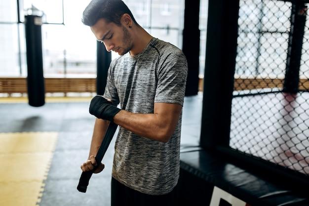 Man gekleed in het grijze t-shirt wikkelt een handverband om zijn hand in de boksschool.