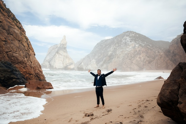 Man gekleed in het pak staat op het strand tussen de rotsen en hij ziet er gelukkig uit