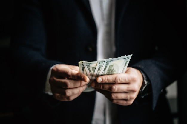 Man geld tellen, man in zakelijke kleding met dollars.