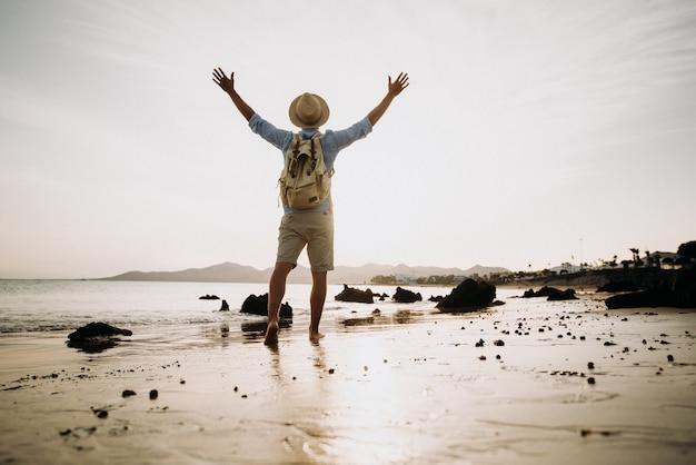 Man geniet van het leven en de vrijheid die armen naar de hemel opent op het strand bij zonsondergang.