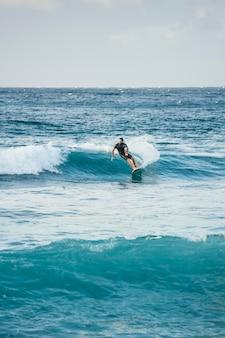 Man geniet van zijn tijd op surfplank tussen de golven
