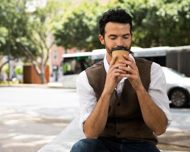 Man genieten van een kopje koffie buitenshuis