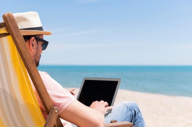 Man genieten van het strand terwijl u werkt aan laptop