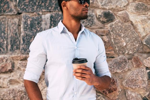 Man genieten van verse koffie. close-up van een knappe jonge afrikaanse man die een koffiekopje vasthoudt terwijl hij buiten tegen de gestenigde muur staat