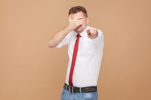 Man gesloten ogen en wijzende vinger naar de camera. business mensen concept, goede en slechte emotie en gevoelens. studio-opname, geïsoleerd op lichtbruine achtergrond