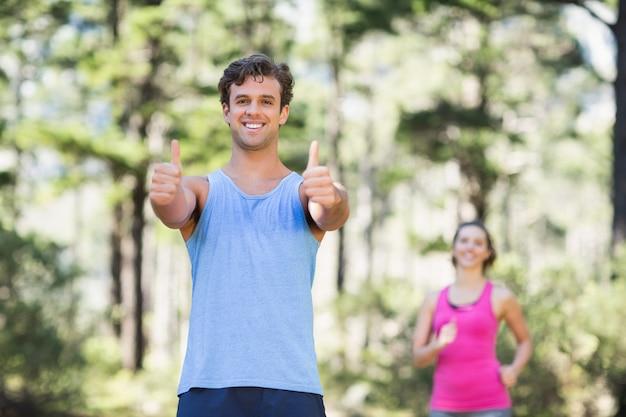 Man gesturing duimen omhoog met vrouw op achtergrond
