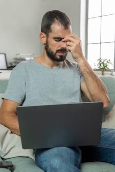 Man gevoel oogpijn tijdens het werken op laptop vanuit huis