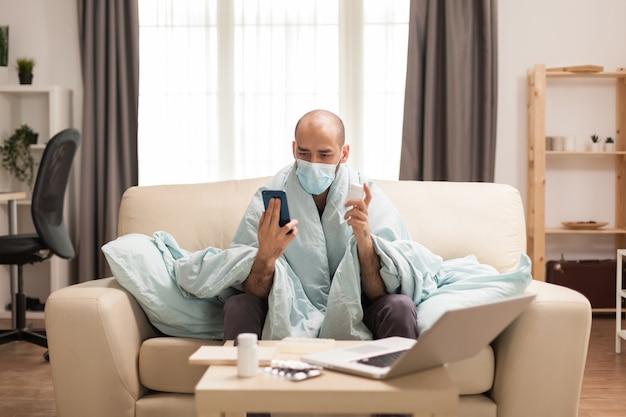 Man gewikkeld in deken met pillenfles in een videogesprek met arts tijdens wereldwijde pandemie.
