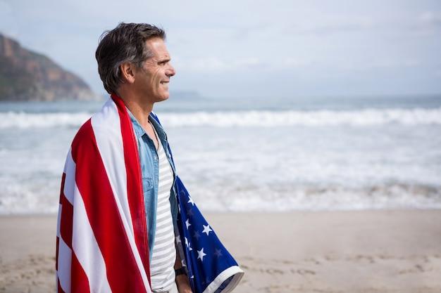 Man gewikkeld in een amrican vlag staande op het strand