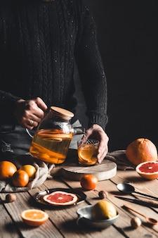 Man giet citrus thee op een houten tafel
