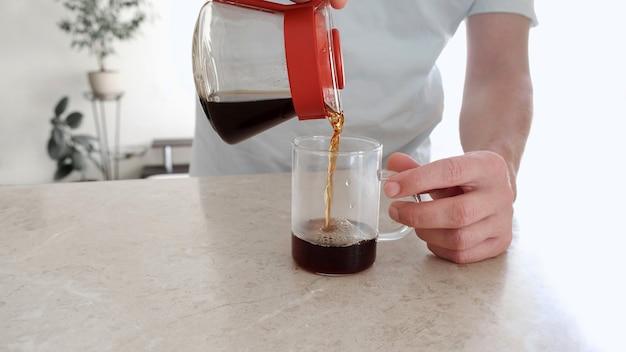 Man giet een vers gezette koffie in een glazen beker van de glazen server. pourover, v60.