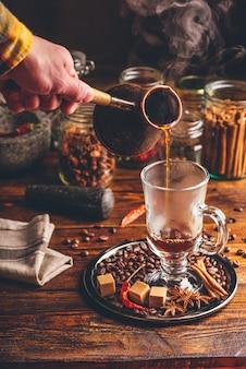 Man giet hete stijgende koffie in glazen mok. oosterse kruiden en koffiebonen op metalen dienblad.