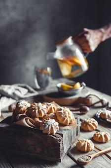 Man giet hete thee met plakjes verse grapefruit op houten achtergrond. gezonde drank, eco, veganistisch