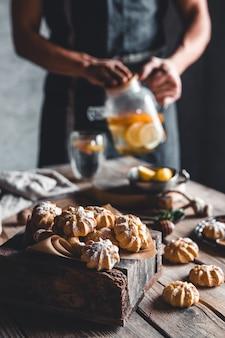 Man giet hete thee met plakjes verse grapefruit op houten muur. gezonde drank, eco, veganistisch