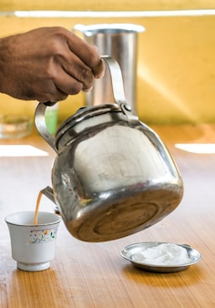 Man gieten chai thee in een beker