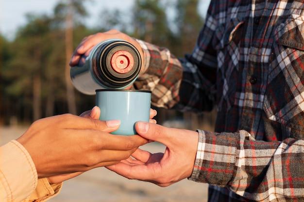 Man gieten koffie voor zijn vriendin close-up