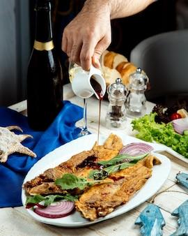 Man gieten nar sharab granaatappelsaus op gebakken vis