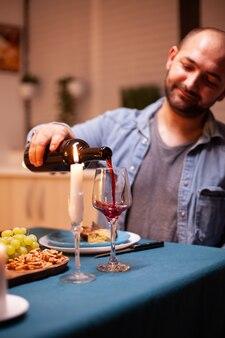 Man gieten rode wijn in glas vieren relatie met vrouw in eetkamer. jonge man die rode wijn in het glas van de vrouw giet. romantisch kaukasisch gelukkig paar zittend aan tafel vieren.