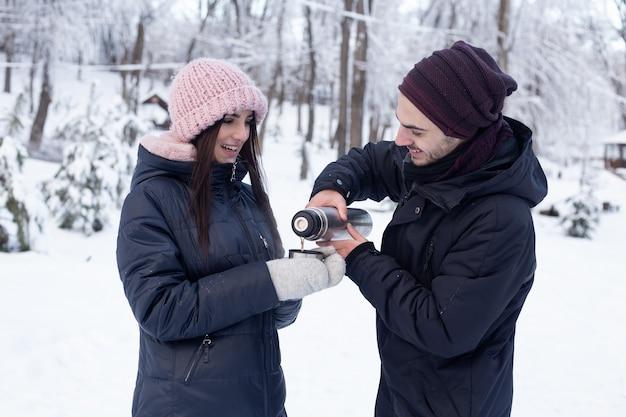 Man gieten thee uit een thermoskan in winter park