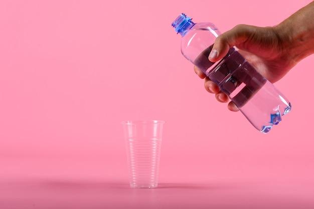 Man gieten van water uit de fles in plastic beker op roze achtergrond