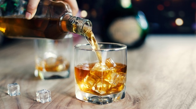 Man gieten whisky in glazen