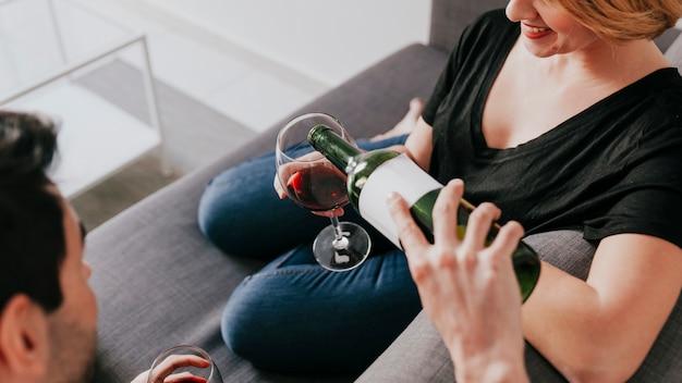Man gieten wijn aan vriendin op de bank