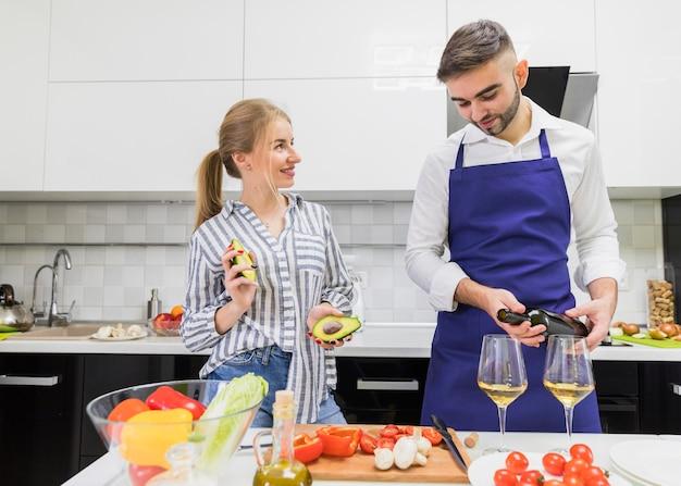 Man gieten wijn in glas in de buurt van vrouw met avocado