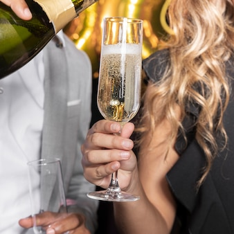 Man gietende champagne in glas dat door vrouwenclose-up wordt gehouden