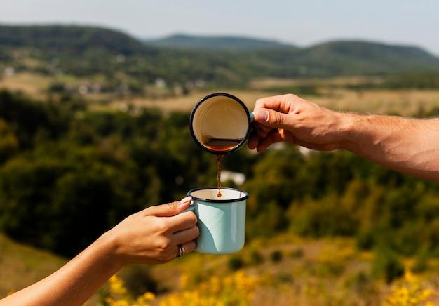 Man gietende koffie in een andere kop die door vrouw wordt gehouden