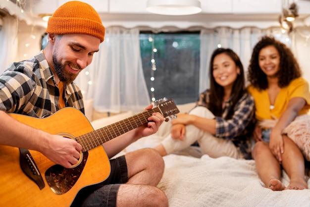 Man gitaarspelen en vrouwen luisteren binnenshuis