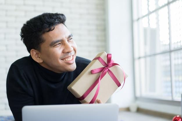 Man glimlachend en cadeau met laptop voor zwarte vrijdag en cyber maandag te houden