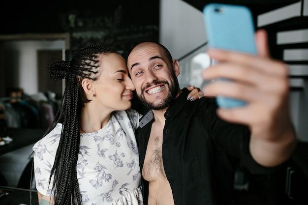 Man glimlachend en het maken van een auto-foto met zijn vriendin