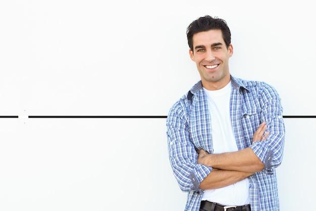 Man glimlachend leunend tegen een witte muur