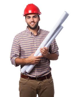 Man glimlachend met een rode helm en blauwdrukken