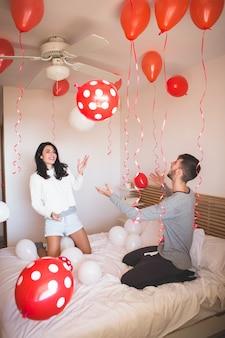 Man glimlachend terwijl zijn vriendin kijkt naar de kamer vol met rode ballonnen