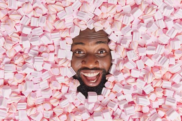 Man glimlacht breed poseert tussen heerlijke roze zachte marshmallows menselijk hoofd door smakelijk dessert