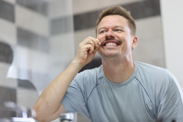 Man glimlacht en houdt zijn snor voor spiegel